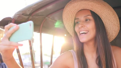 Young Hipster Girl Doing Mobile Phone Selfie Photo in Bicycle Rickshaw Taxi with Amazing Lens Flare Sunset Effect on Background. Thailand. 4K, Slowmotion.
