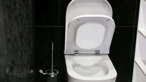 soft closing of the toilet lid in the bathroom. Modern interiors and technology in the bathroom
