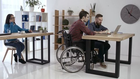 Skillful disabled man in wheelchair discussing new startup project on laptop pc with coworker while asian female colleague talking on phone in creative office. Handicapped freelancer working in office