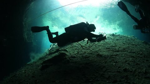 Cave divers swimming in undeground passages. Cenote underwater diving in Mexico.