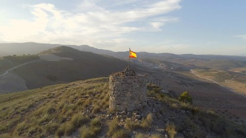 Flight Over an Abandoned Spanish Watchtower With a Flag Flying and Beautiful Surrounding Mountainous Landscape