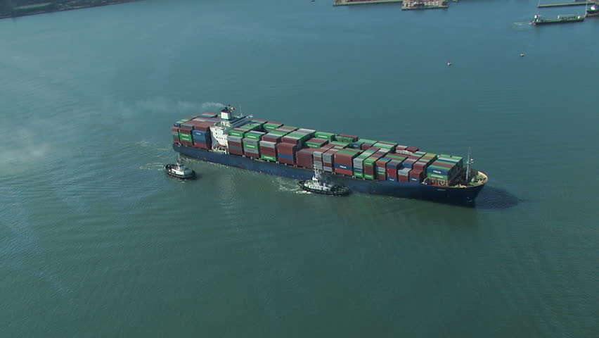 Aerial of cargo ship being assisted by tug boats and fully loaded with