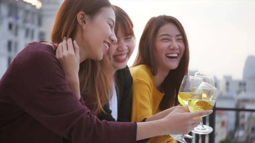 Outdoor shot group of happy teen people having fun toasting drinks sit together on rooftop terrasse at sunset. Young asian lady friends hanging out, Holiday celebration festive party. 4k resolution.