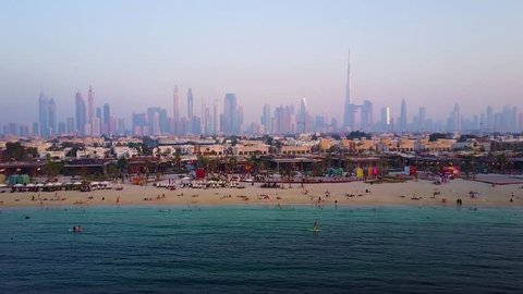 Tourists relax on city beach in Dubai aerial view. People relaxing on Jumeirah beach in Dubai Marina luxury hotels, United Arab Emirates