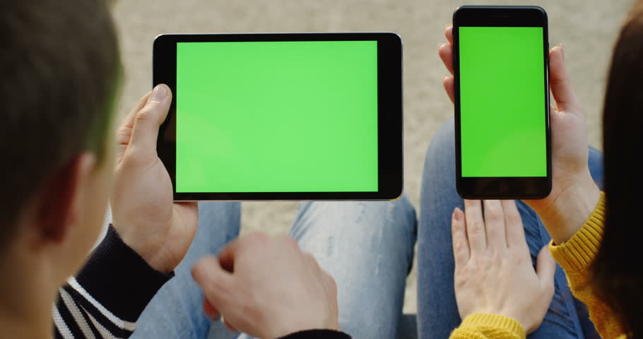 Over shoulder view of the man's hands scrolling on the black tablet device and woman's hands on the black smartphone with green screen. Chroma key. Close up. | Shutterstock HD Video #33503176