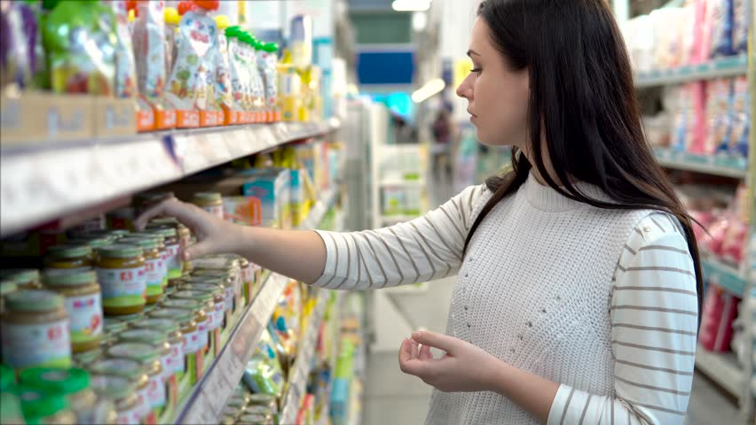 Young woman chooses baby food in the supermarket, Mother chooses food for their child in the market, girl stands near the supermarket shelf and selects the products | Shutterstock HD Video #33505546