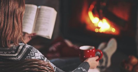 Woman Reading a Book by the Fireplace. SLOW MOTION 4K. Young woman reading a book by the warm fireplace decorated for Christmas. Relaxed holiday evening concept.