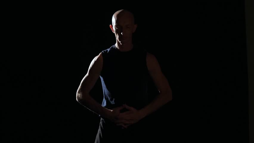 Half-lit silhouette of a man stretching in a darkened room with a single source of light. He is stretching his arms, legs, hands and chest.