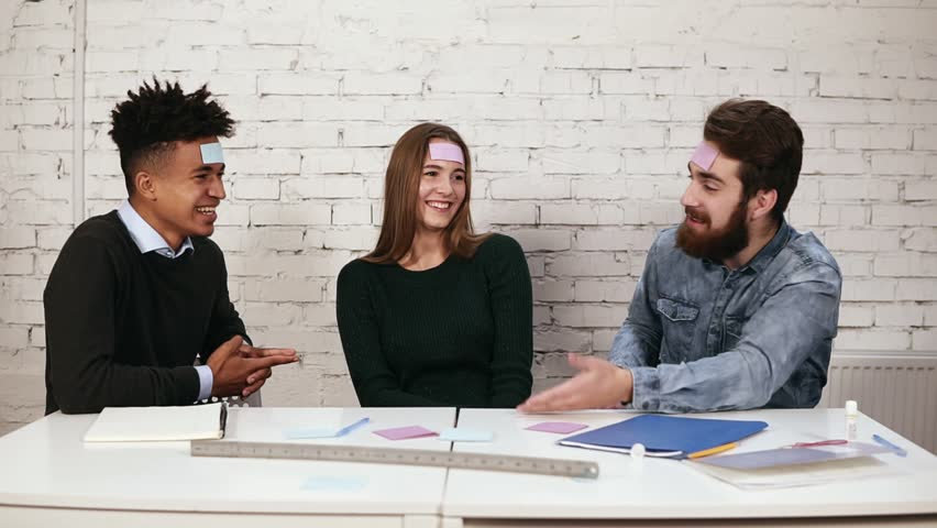 Young people pasted pieces of paper on forehead and guess words. Company of friends having fun in the office. Diverse business team playing games in the office. Slowmotion shot