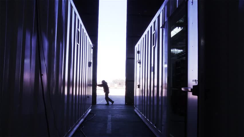 Man Opening the Door of a Container Warehouse. View from Inside.  #33540646