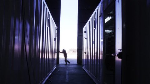Man Opening the Door of a Container Warehouse.