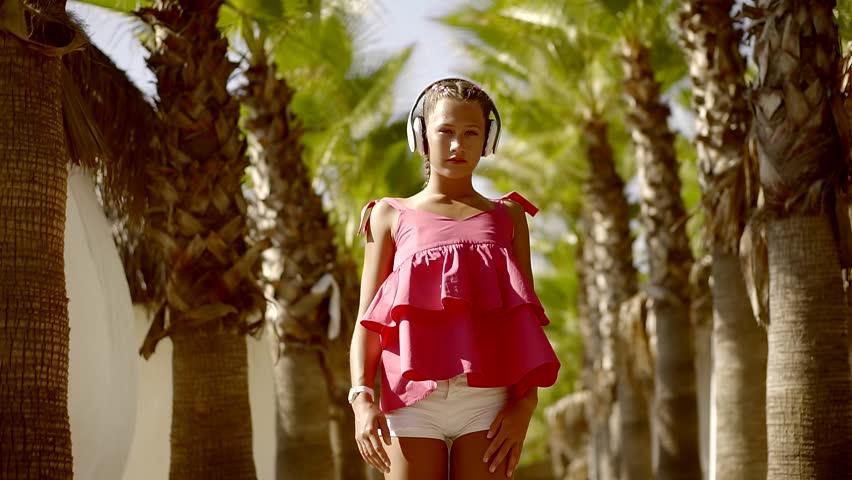 Slender Young Cute Teen Girl Dancing Broken Dancing In The Tropical Gardens Listening To Music In Big Headphones White