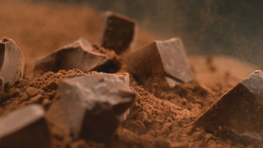 Chunks of chocolate falling into powdered chocolate, shot with high speed camera.