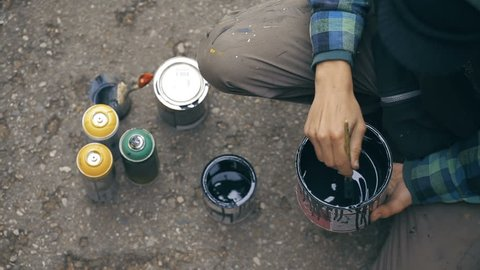 Close up shot of Artist who stir a black paint into a can and pouring it to another can on the ground. View from top