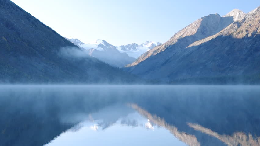 Beautiful mountain range with snow on the peak are reflected in foggy lake