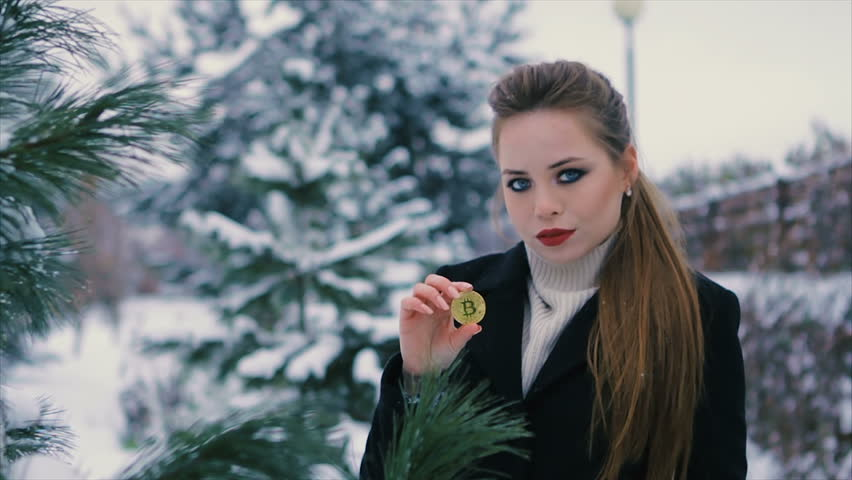9f96aa953f6e close up of Brunette fashionable sexy pretty rich woman holds a golden  bitcoin in hands outdoor. Winter time. Slow motion.