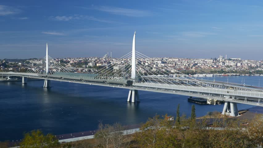 Time lapse shot of modern cable stayed Halic metro bridge at morning time. Subway trains run across Golden Horn, lively car traffic on Ataturk bridge behind. Renovated embankment with park on fore