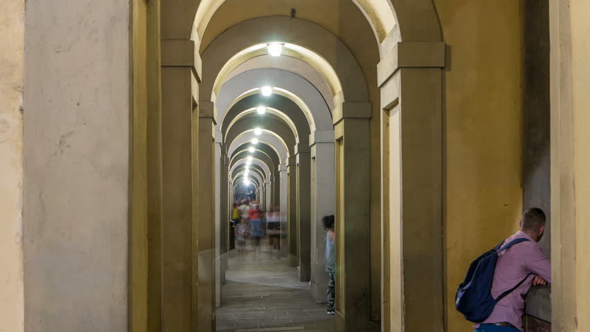 Arches of the Vasari Corridor night timelapse in Florence, Italy. The Vasari Corridor is the famous passageway which connects the Palazzo Vecchio with the Palazzo Pitti. People walking inside