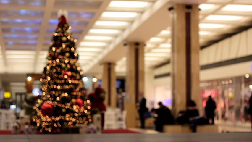 Christmas-tree in a shopping center with walking peoples. Video out of focuse