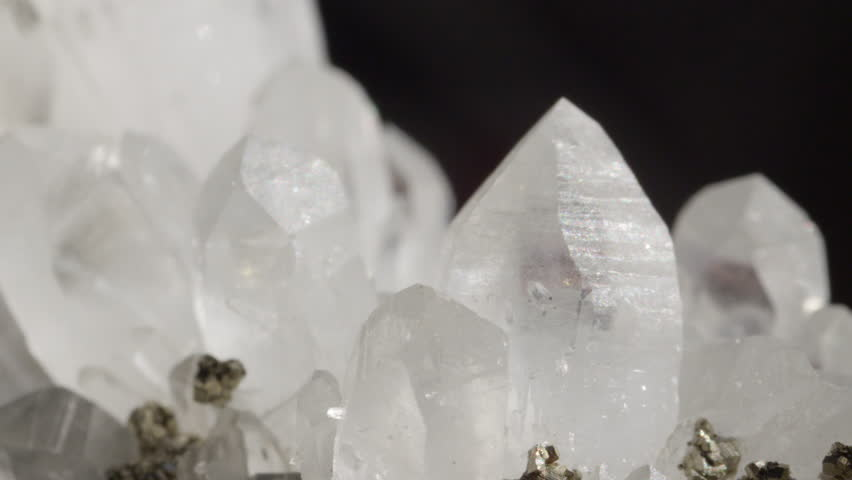 CLOSE UP DOF: Detailed close up of charming opaque white quartz in combination with golden pyrite particles. Shiny gemstones together forming a beautiful sight. Ice like structure of quartz and pyrite
