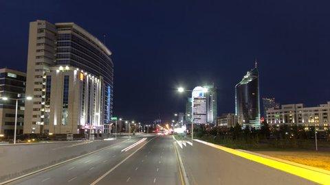 Night city traffic Kunaev Avenue timelapse hyperlapse. Modern building illuminated by night on background. Astana, Kazakhstan