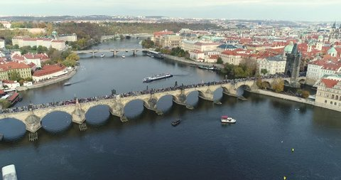 Panoramic view from above to the city of Prague and Charles Bridge, tourists on the Charles Bridge, flying over the river along, Panoramic view from above, Vltava River, flight over the Charles Bridge