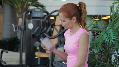 Portrait of red-haired woman who drinks a cocktail at the gym. Young slender female athlete in pink suit takes a sip of protein drink in fitness studio against background of green plants.
