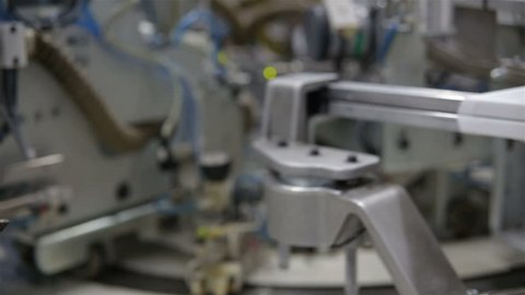 Robotic Arm in Action. Hosiery Manufacturing. Robotic arm working on factory assembly line.Industrial Mechatronics. Automated Production in Factory. Tights Manufacturing Workshop. Industrial Robot.