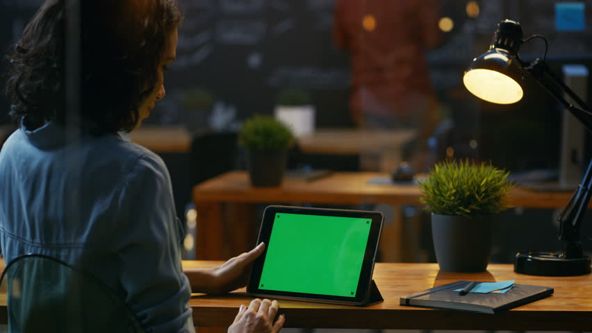 Young Woman Sits at Her Wooden Desk Uses Tablet Computer with Mock-up Green Screen, She Uses Various Swipe and Touch Gestures.  | Shutterstock HD Video #33748606