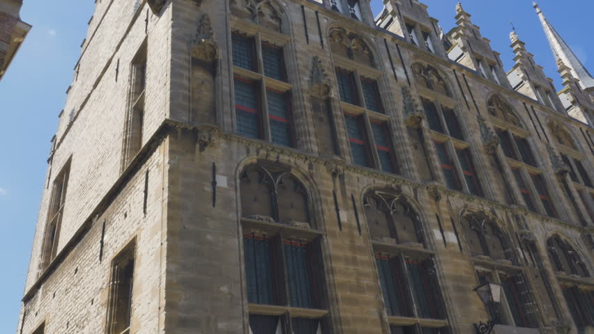 The exterior details of the Middelburg town hall edifice. A display of the exquisite architecture filmed from a low angle on a bright summer day.