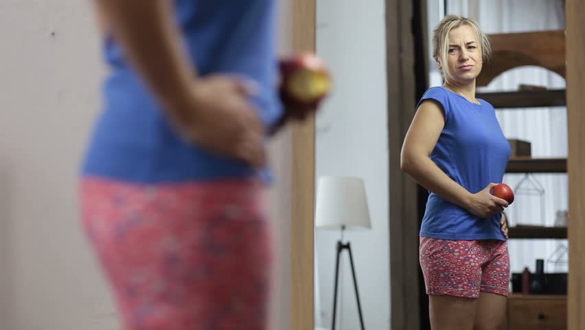 Upset woman eating apple and looking at her reflection in the mirror, displeased and dissatisfied with her body shape in bedroom. Sad girl pinching stomach fat while looking at herself in the mirror.