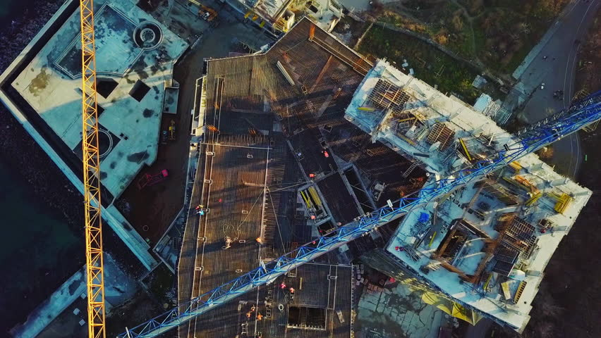 Aerial city view. Construction of a high-rise skyscraper on the ocean by two cranes. The camera is pointing down. Flies horizontally from the subject.