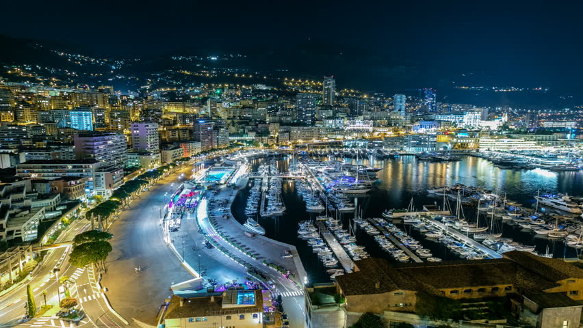 Panorama of Monte Carlo timelapse at night from the observation deck in the village of Monaco with Port Hercules. Buildings with illumination and yachts in harbor aerial top view. Traffic on the road