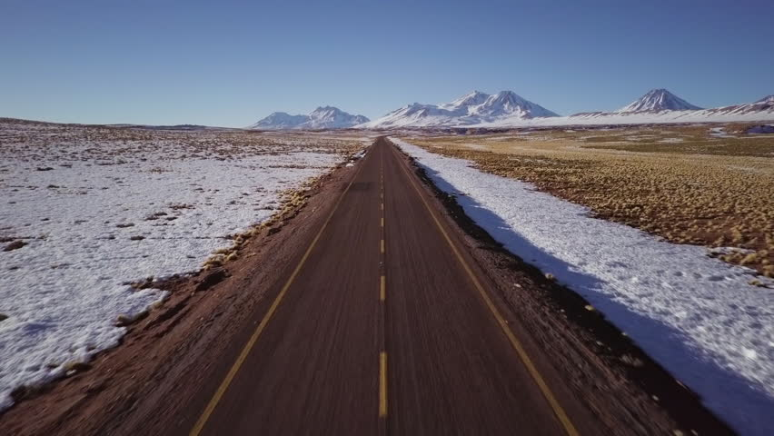 Car drives past drone shot of desolate road in northern Chile
