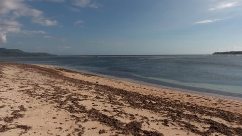 Aerial shooting of beach with seaweed and blue water surface on reef  in tropical environment, footage of beautiful skyline over ocean shallow and calm waves on coral reef near sandy beaches