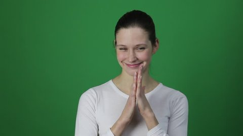 Liar and cunning funny woman looking at camera with cheater look. Studio shot, isolated in light green background