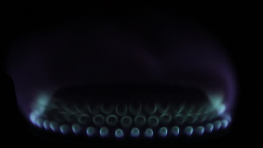 Natureal gas flame on the black background. Natural gas inflammation in stove burner, close up view, Gaz fire burns, house gas flames, motion footage. Dark background, gas red flames. 4K, ULTRA HD.