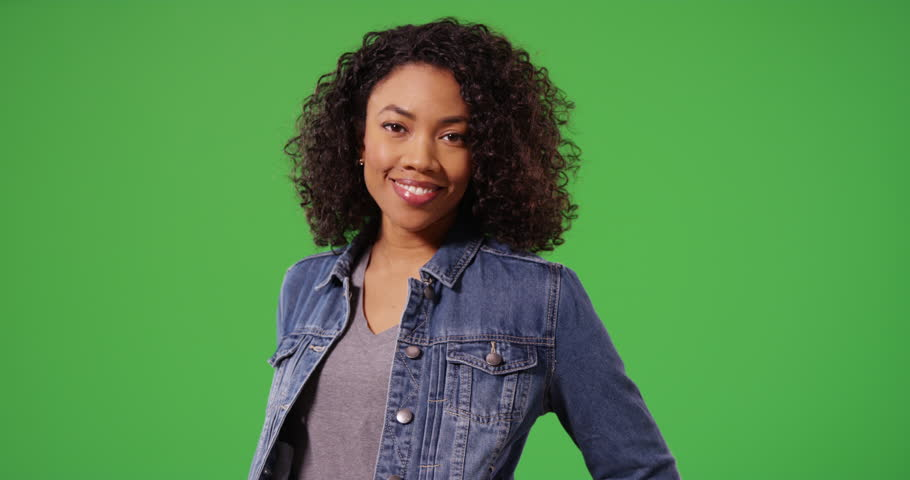 Portrait of happy black woman in jean jacket posing playfully on green screen. Close up of stylish African American Millennial girl smiling and laughing on greenscreen for keying or compositing. 4k | Shutterstock HD Video #33810436