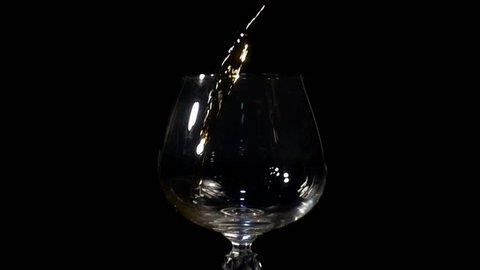 Cognac is poured into a glass in Slow Motion on a black background