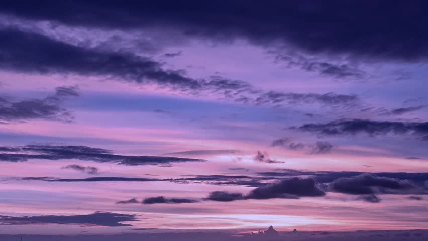 Dark purple clouds day to night sky time lapse. Purple black clouds pass fly sky time lapse background. Purple sky clouds afterglow dusk evening time lapse. Video footage purple clouds sky time lapse.