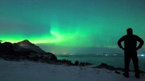 Northerrn lights in Iceland - aurora borealis with man silhouette time lapse 4K