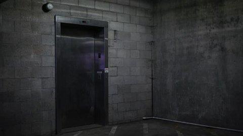 An Elevator door opens in the basement ground level of dark parking garage