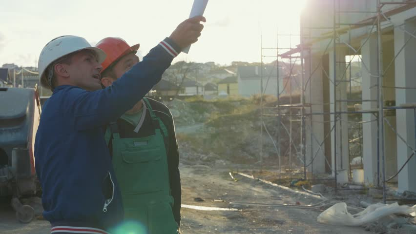Construction worker and engineer talking at construction site site. Workers in helmets at building area at sunset, slow motion.