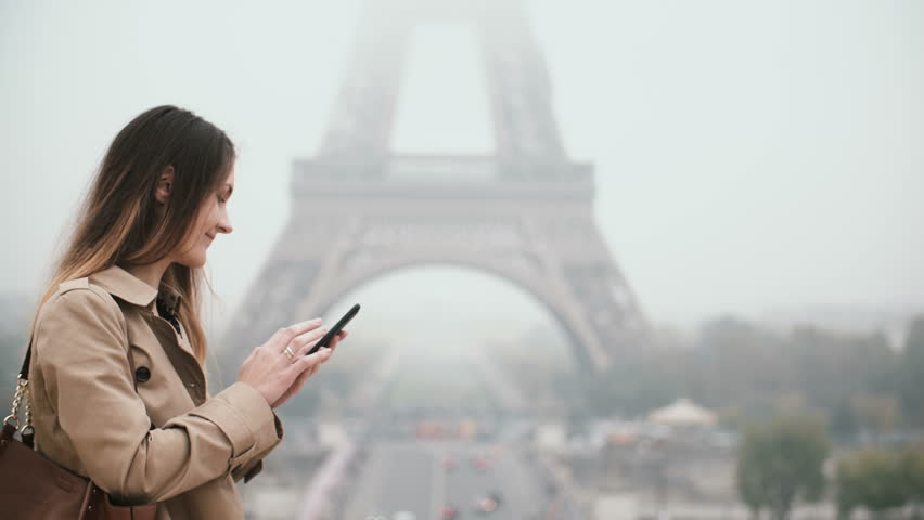 Young beautiful woman with mobile phone in foggy morning. Female using smartphone near the Eiffel tower in Paris, France   Shutterstock HD Video #33864016
