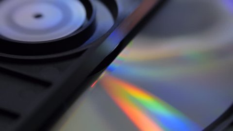 CD, DVD are insert in the player and start rotation. Different color of reflection from the disk. Macro. Closeup. Shallow depth of field
