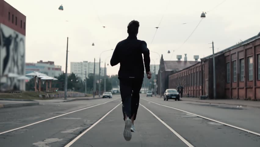 Man running in the middle of the street. Background shot. Slow motion. Abstract concept of individual success and fame. #33920146