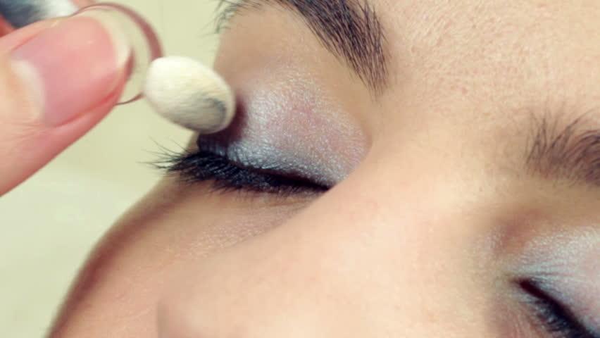 Make-up artist applying make-up on model