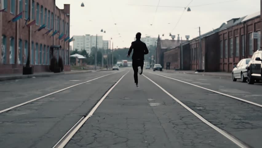 Man running fast in the middle of an old street. Real time shot. Freedom. Camera follows sportsman between tram tracks. #33943636
