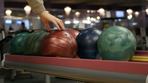 Close-up of varicolored bowling balls, woman takes ball