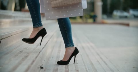 close-up of female legs in high heels walking on the stairs